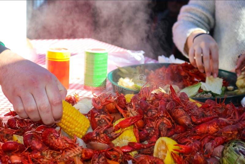 到达为玉米棒子片断的手从堆的通入蒸汽的食物在小龙虾煮沸用另一手采摘食物 免版税库存图片