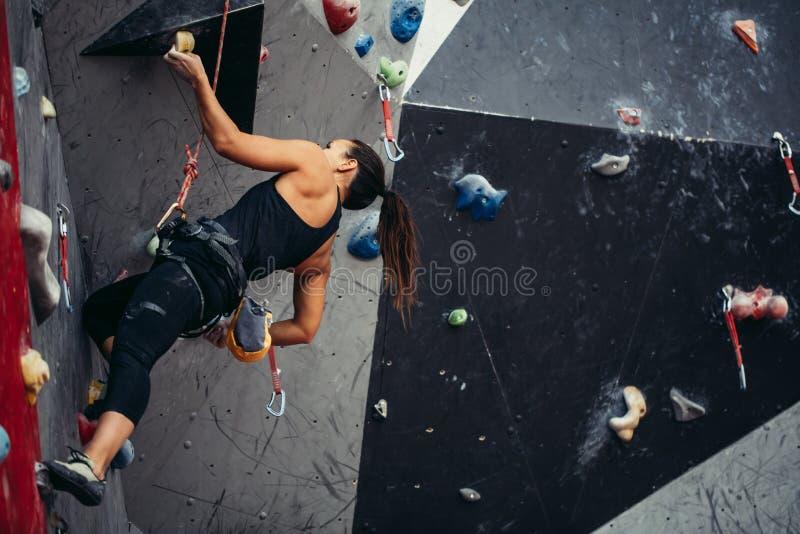 到达人为bouldering的墙壁的上面妇女,当行使在健身房时 图库摄影