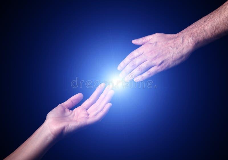 到达和感人的手 与感人的指尖的明亮的轻的星火光 免版税库存图片