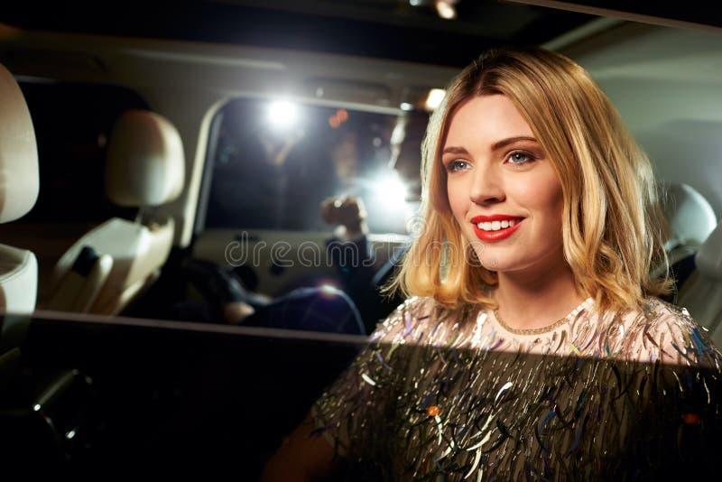 到达在大型高级轿车的名人夫妇,拍摄由无固定职业的摄影师 库存图片