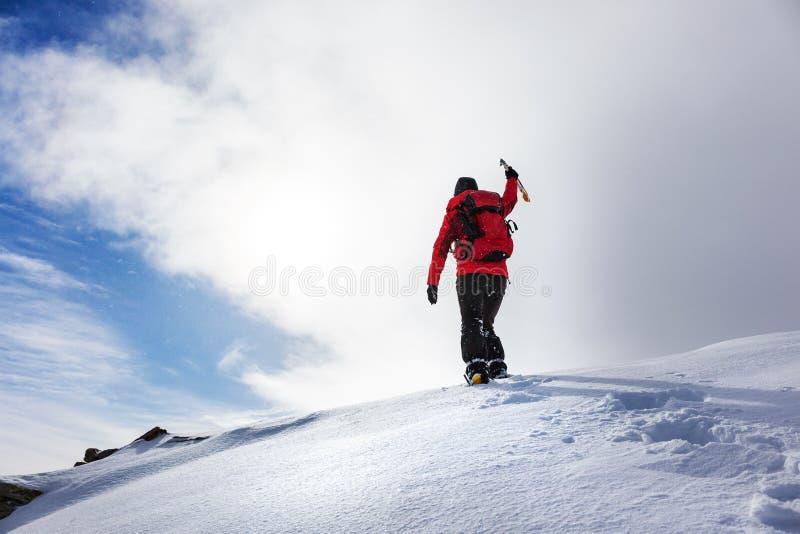 到达多雪的山峰的山顶的在冬天季节的登山家 库存照片