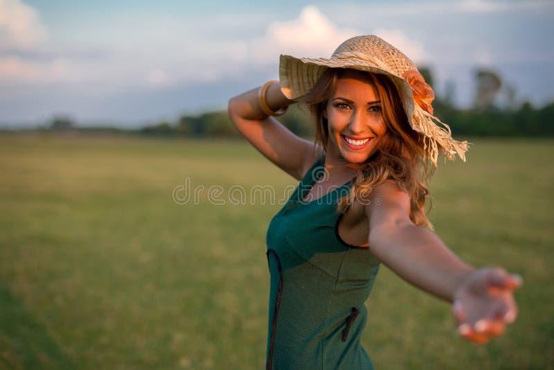 到达她的在领域的美丽的年轻愉快的妇女手,当s时 库存图片