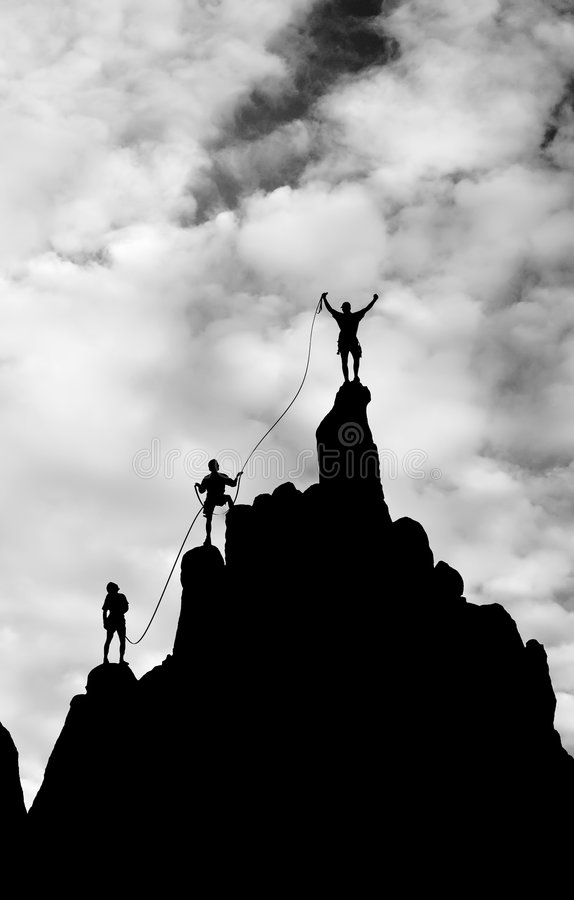到达山顶小组的登山人 库存照片