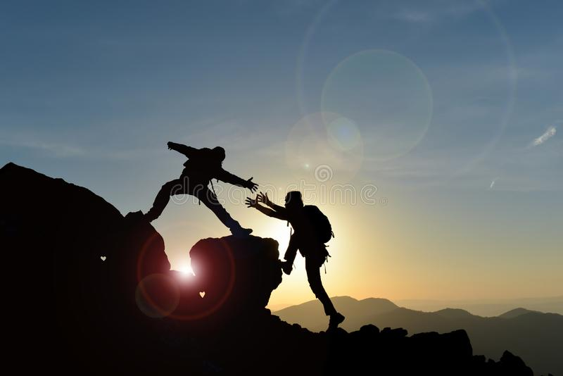 到达山顶的登山人在日落 免版税图库摄影