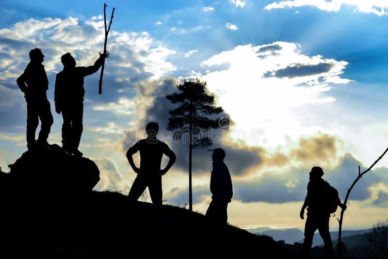 到达山顶的远足者在日落 免版税图库摄影