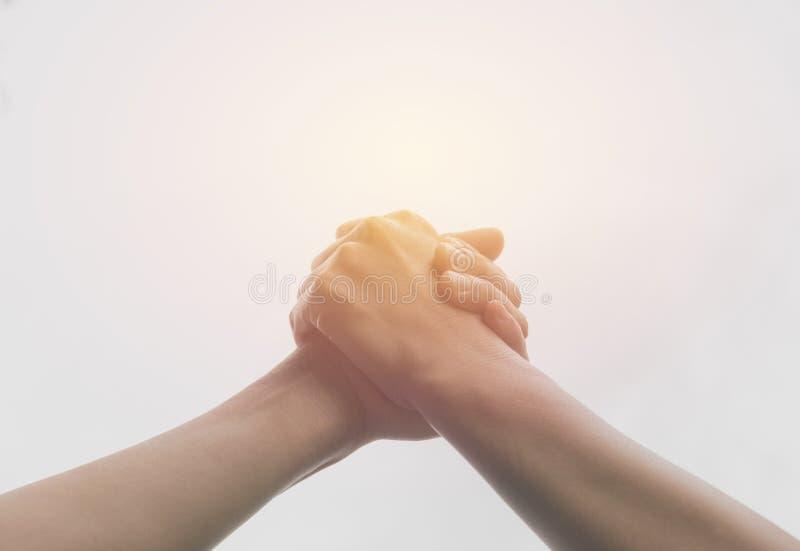到达往彼此的两只手 配合和帮助 库存照片