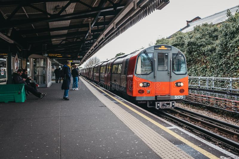 到达戈尔德费尔德地铁车站,伦敦,英国一个室外平台的伦敦地铁火车  免版税库存照片