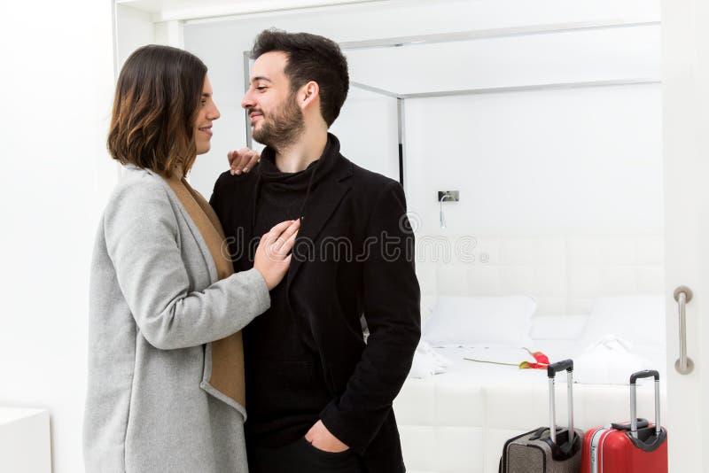 到达旅馆套房的英俊的夫妇 免版税库存照片