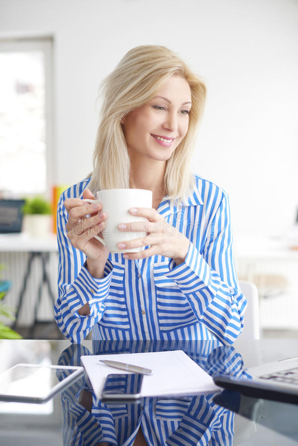 到达的生意人咖啡杯服务台重点递藏品早晨办公室被安置的手提箱 图库摄影