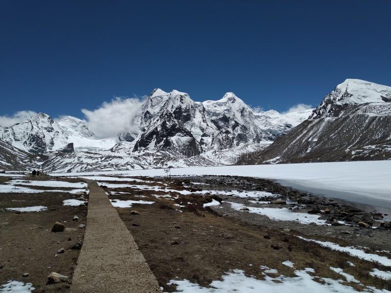 到达美丽的山,沿冻结的llake的边 免版税库存照片