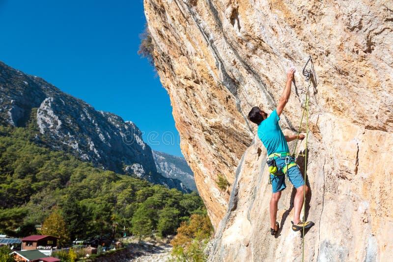 到达自然岩石的成熟男性登山人举行 免版税库存图片