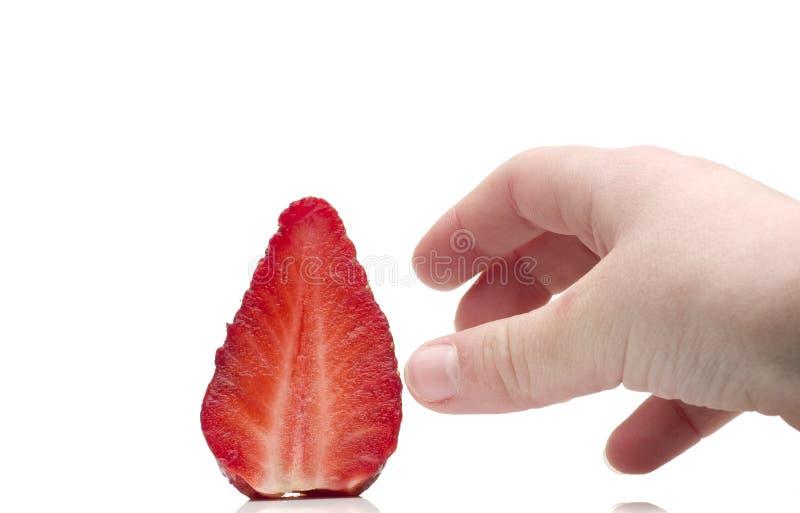 到达草莓的孩子的手 使上瘾从草莓 免版税库存图片