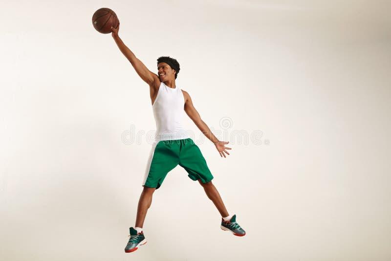 到达高为篮球的微笑的年轻黑人 库存照片