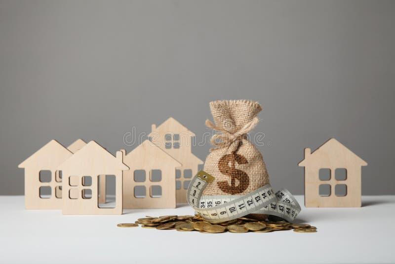 制作与美元商标的袋子在黄色硬币和测量在房子图背景的磁带  Ð攒钱¡ oncept什么时候 免版税库存图片