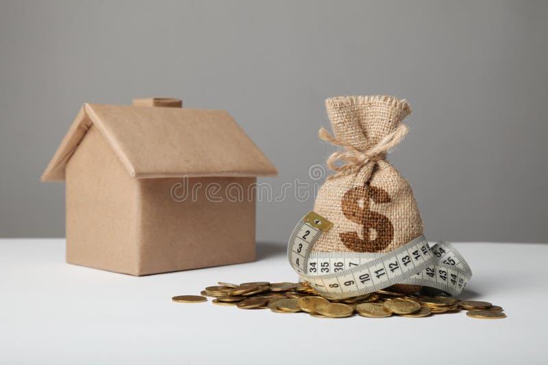 制作与美元商标的袋子在黄色硬币和测量在房子图背景的磁带  Ð攒钱¡ oncept什么时候 库存照片