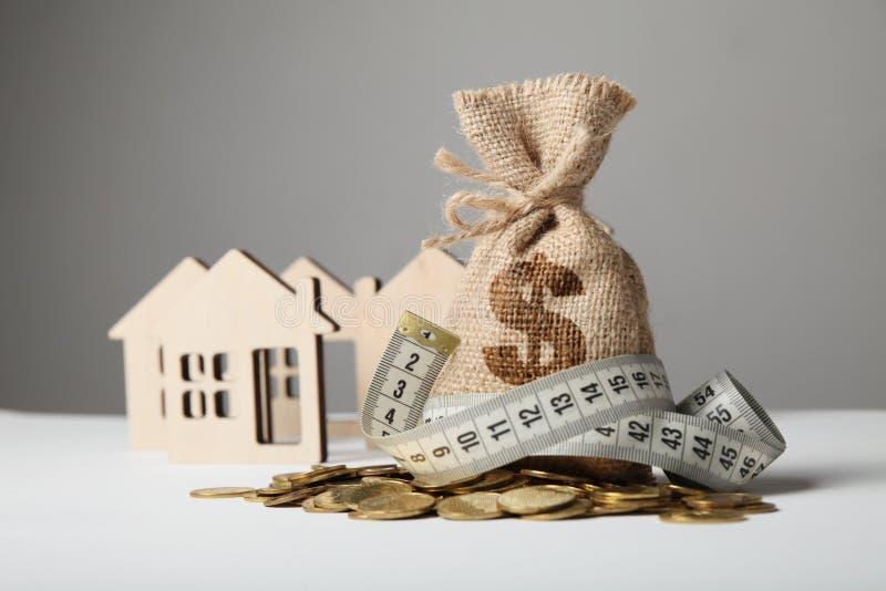 制作与美元商标的袋子在黄色硬币和测量在房子图背景的磁带  攒钱Сoncept什么时候 免版税图库摄影