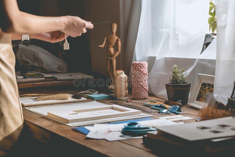 制作书的美好的妇女手在与文具的桌面 免版税库存照片