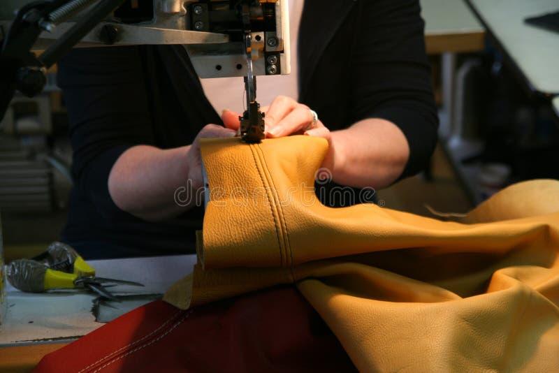 制作女性皮革设备缝合的工作者 图库摄影