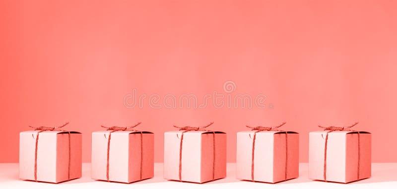 制作纸板在坚实桃红色背景的礼物盒 假日和礼物概念 流行艺术slyle 居住的珊瑚题材-颜色  免版税库存照片