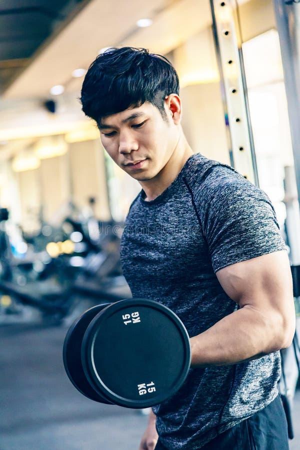 制定出举的重的哑铃的年轻亚裔人在健身健身房 免版税图库摄影