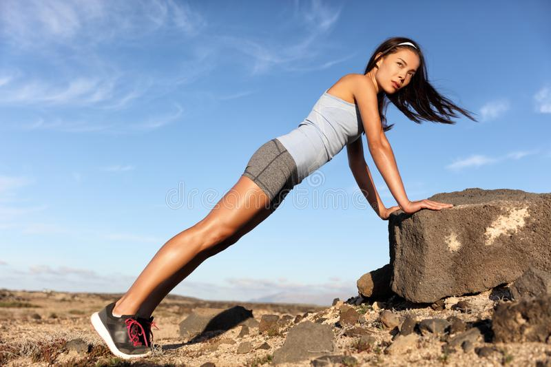 制定出胳膊的健身亚洲妇女俯卧撑板条 库存照片