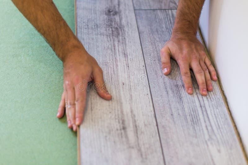 制定层压制品的台面厚木板的杂物工,当更新房子时 递特写镜头 免版税图库摄影