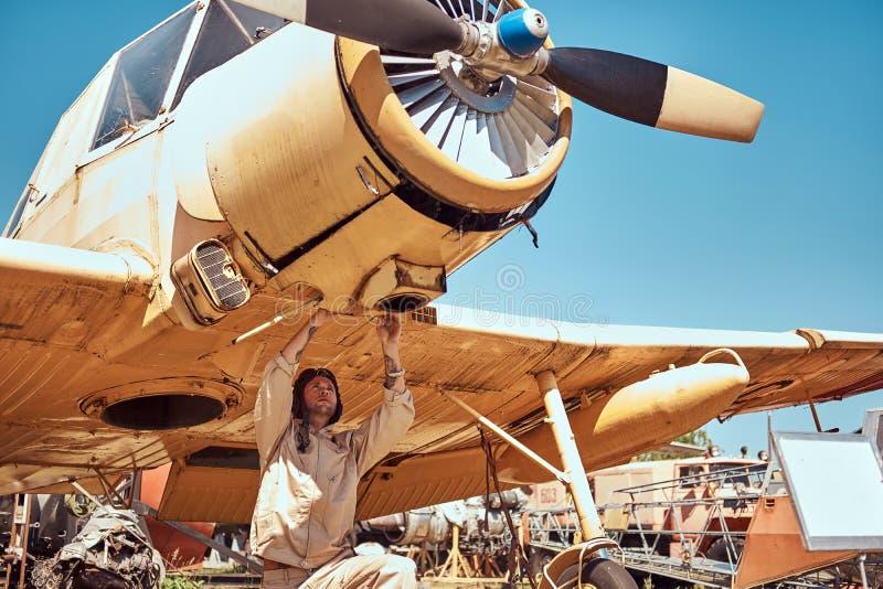制服和飞行盔甲的技工露天修理减速火箭的军事飞机博物馆 免版税库存照片