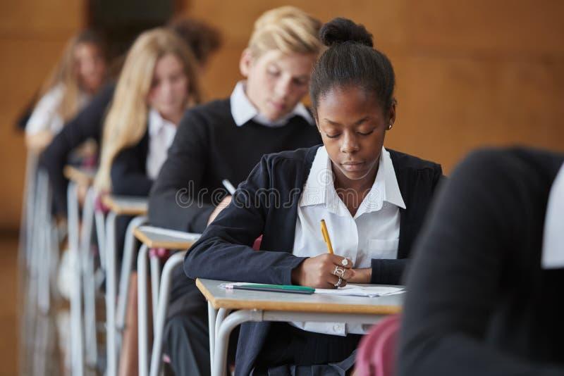 制服坐的考试的少年学生在学校霍尔 库存照片