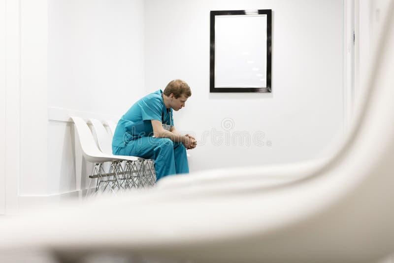 制服的体贴的护士坐椅子在医院走廊 免版税库存图片