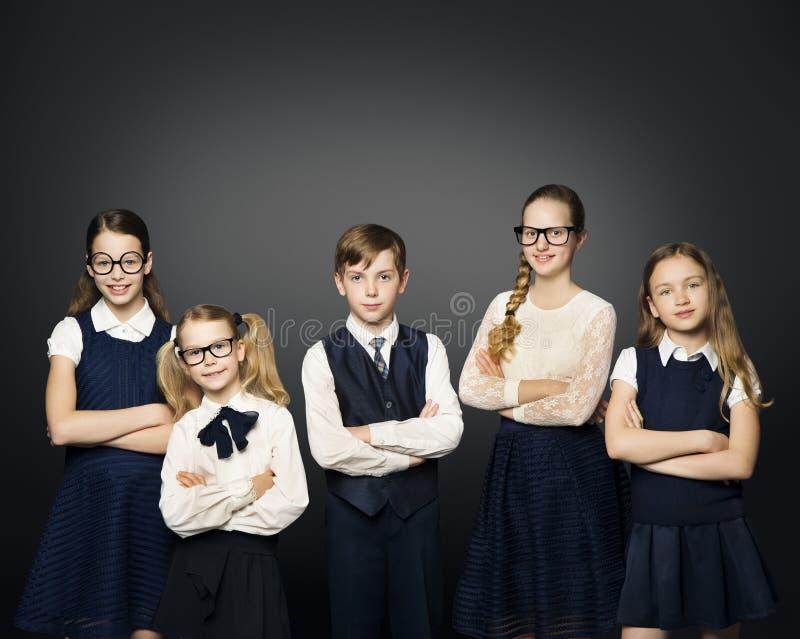 制服的小学生小组、女孩和男孩学生在Bl 免版税库存照片