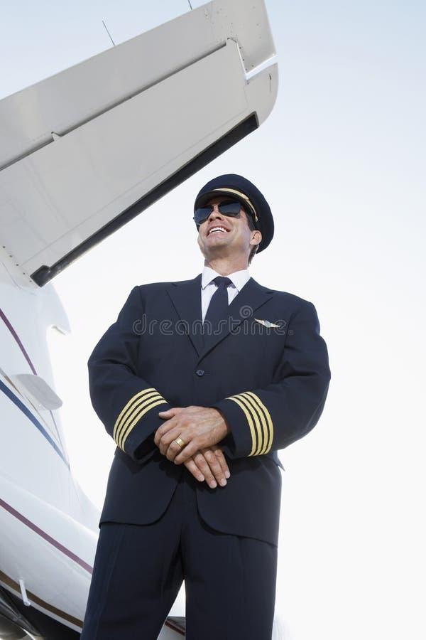 制服的微笑的飞行员在飞机旁边 库存图片
