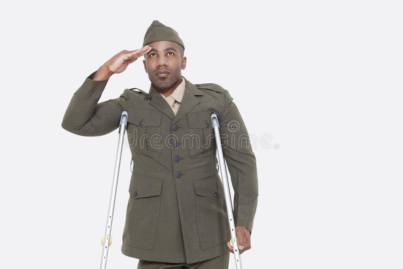 制服的残疾非裔美国人的军官向致敬在灰色背景 图库摄影
