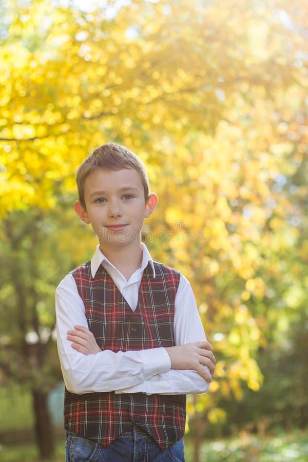 制服的男小学生在秋天黄色树背景 库存图片