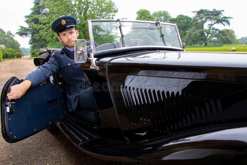 制服的男性空军队官员飞行员留下Britiish豪宅并且上升入他的葡萄酒跑车 库存照片