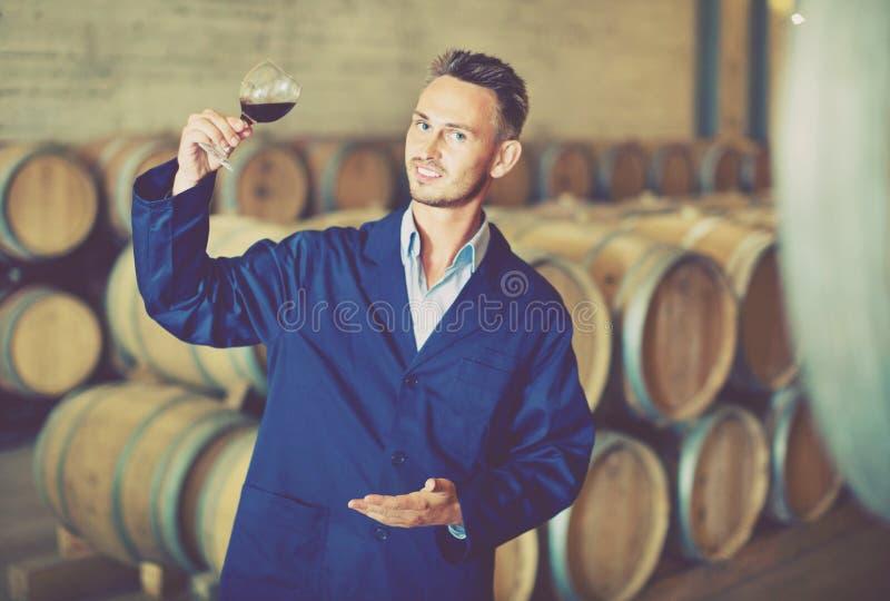 制服的男性酿酒商饮用杯酒在细胞的手 库存照片