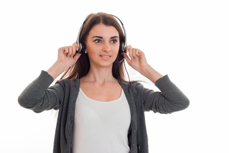 制服的年轻可爱的在白色隔绝的女商人有看起来的耳机和的话筒的去和微笑 免版税库存图片
