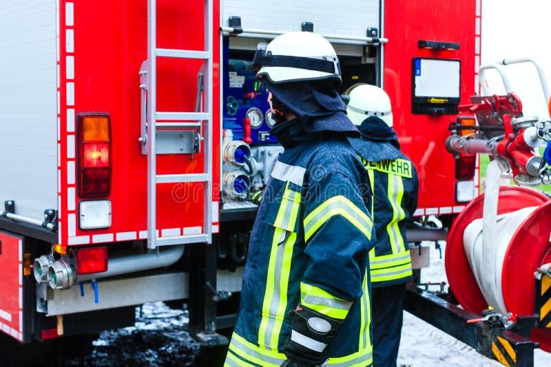 制服的年轻消防员在救火车前面 库存照片