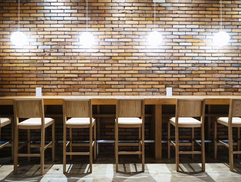 制表与椅子的逆酒吧并且点燃砖墙背景 库存图片