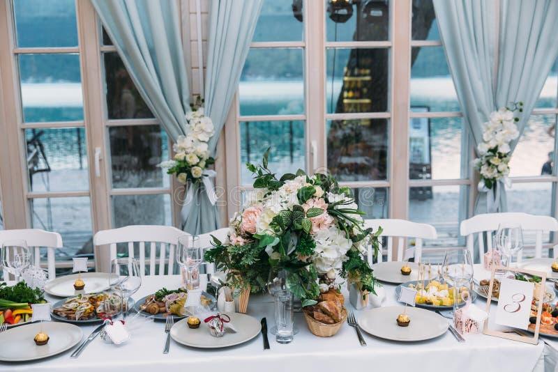 制表与花的设置在结婚宴会,桌和食物在餐馆 婚礼或党的概念 库存图片