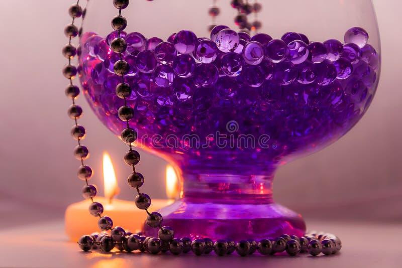 制表与蜡烛、紫罗兰色胶凝体球和小珠的装饰 免版税库存图片