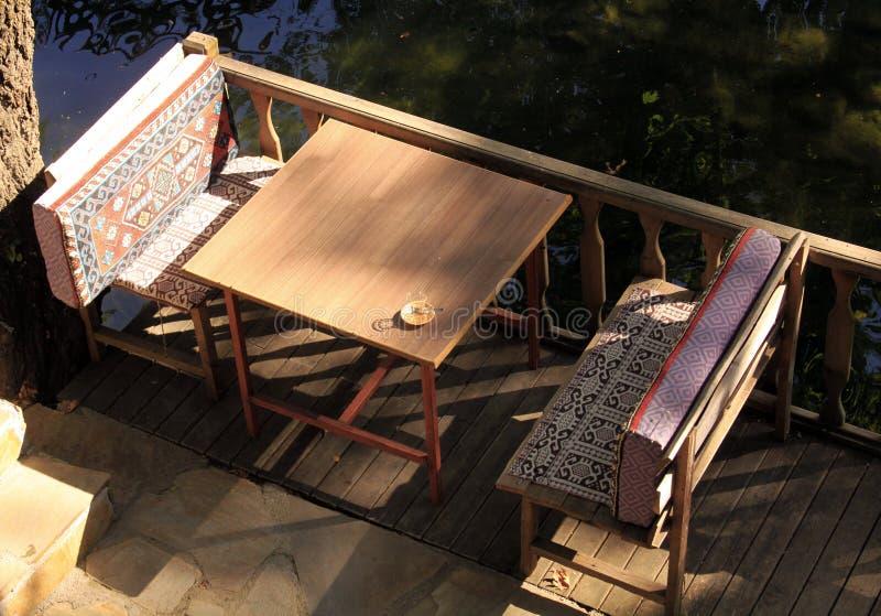 制表和与咖啡杯的两条长凳,接近水 库存图片