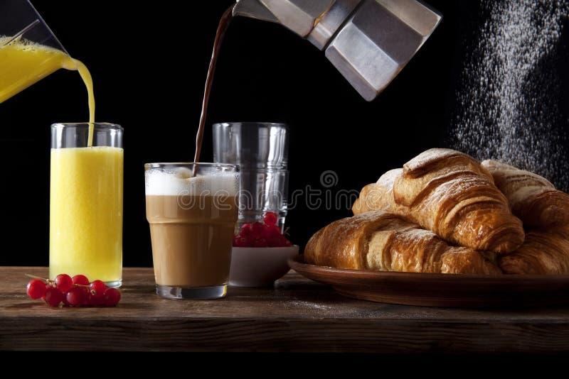 制表早餐新鲜的热的新月形面包,倾吐的橙汁, pou 库存照片