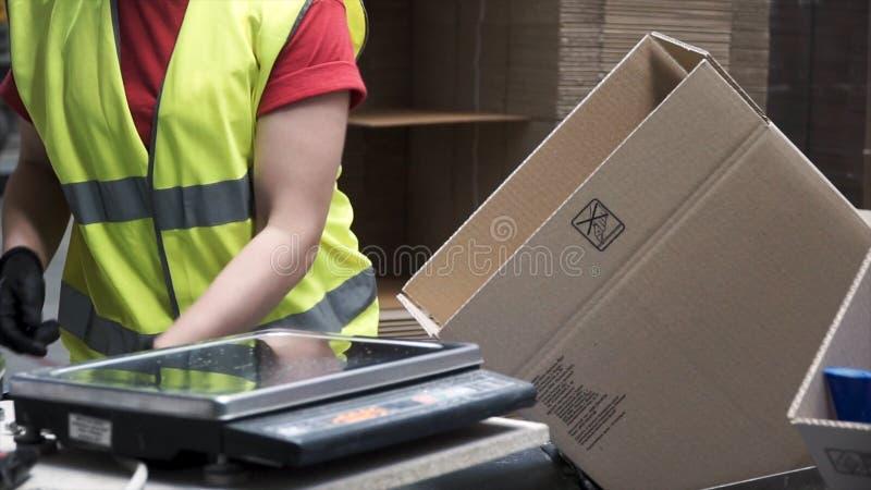 制造业工作者的手的特写镜头视图投入被包装的产品的在纸板箱,在出口前或 图库摄影