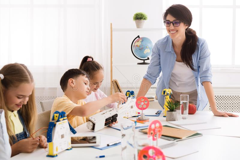 制造机器人车在老师的帮助下的孩子 库存照片