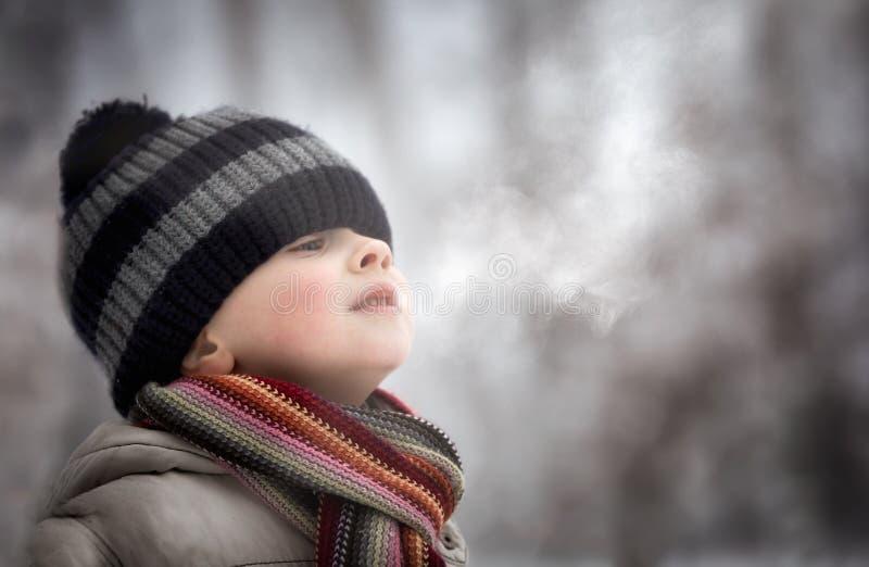 制造水蒸汽的年轻男孩由他的嘴 库存照片