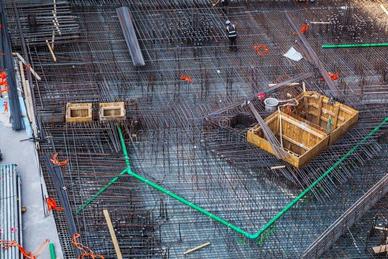 制造钢增强酒吧的建筑工人在建造场所 免版税库存图片