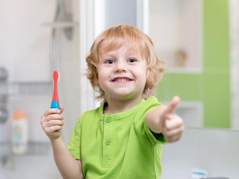 刷他的牙的小孩男孩在卫生间里 举行牙刷和显示的微笑的孩子赞许 免版税库存图片