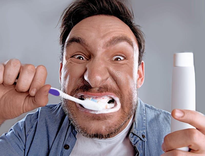 刷他的牙的滑稽的人 免版税库存照片