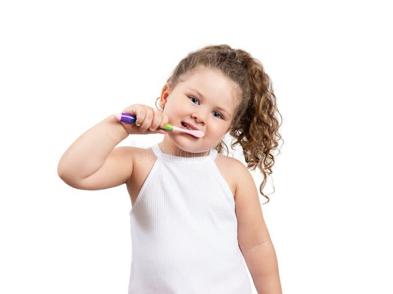 刷她的在被隔绝的白色背景的逗人喜爱的白肤金发的女孩牙 库存图片
