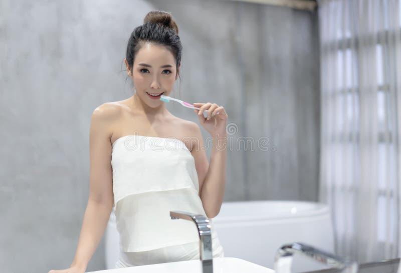 刷她的有一把牙刷的牙在她的卫生间镜子前面和看照相机的年轻美丽的亚裔妇女 ?? 免版税图库摄影